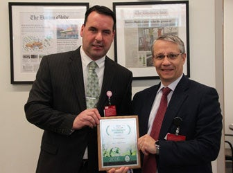 Two gentlemen holding the Emerald Award from Practice Greenhealth