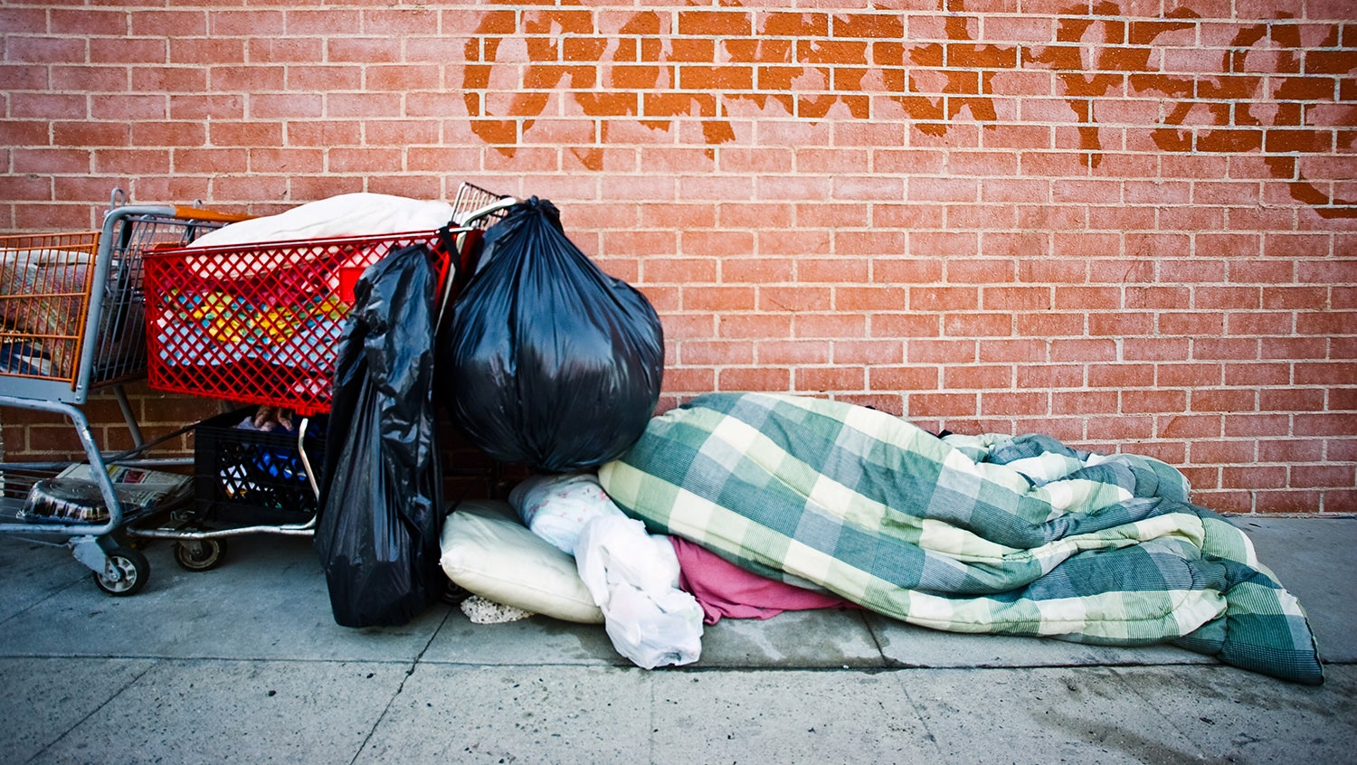 homeless person's belongings and bedding on street sidewalk