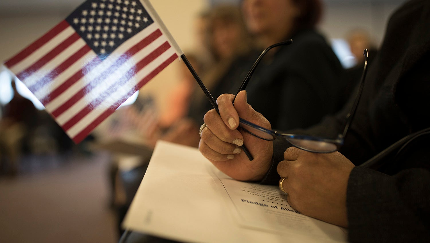 Woman holds American flag during a naturalization ceremony