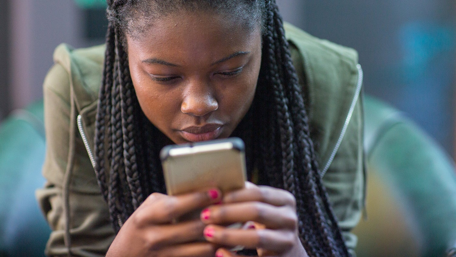 Young black woman stares intently at smartphone screen in her hands