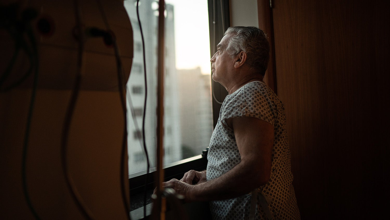 Man in hospital gown looks out room window