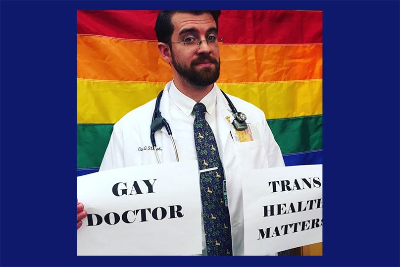Dr. Carl Streed holding sign that says gay doctor trans health matters