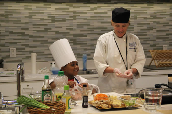 chef helping a child cook