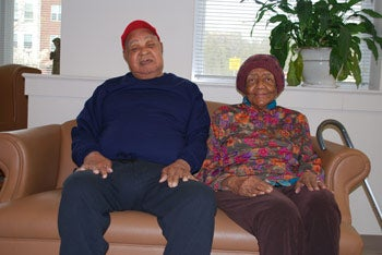 two older individuals, a man and a woman, sitting on the couch