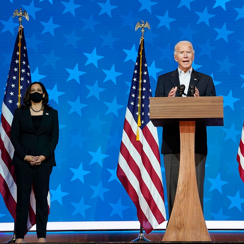 Biden and Harris stand on stage flanked by American flags