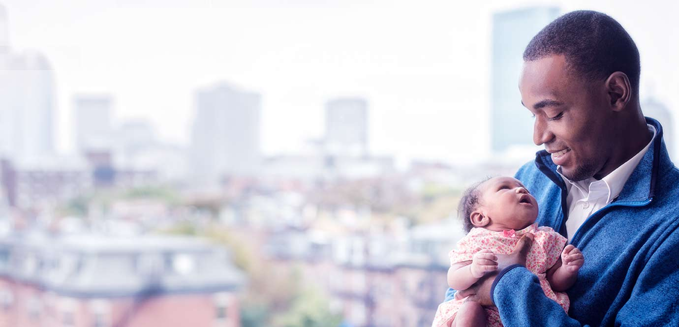 A new father holding his baby with Boston in the background