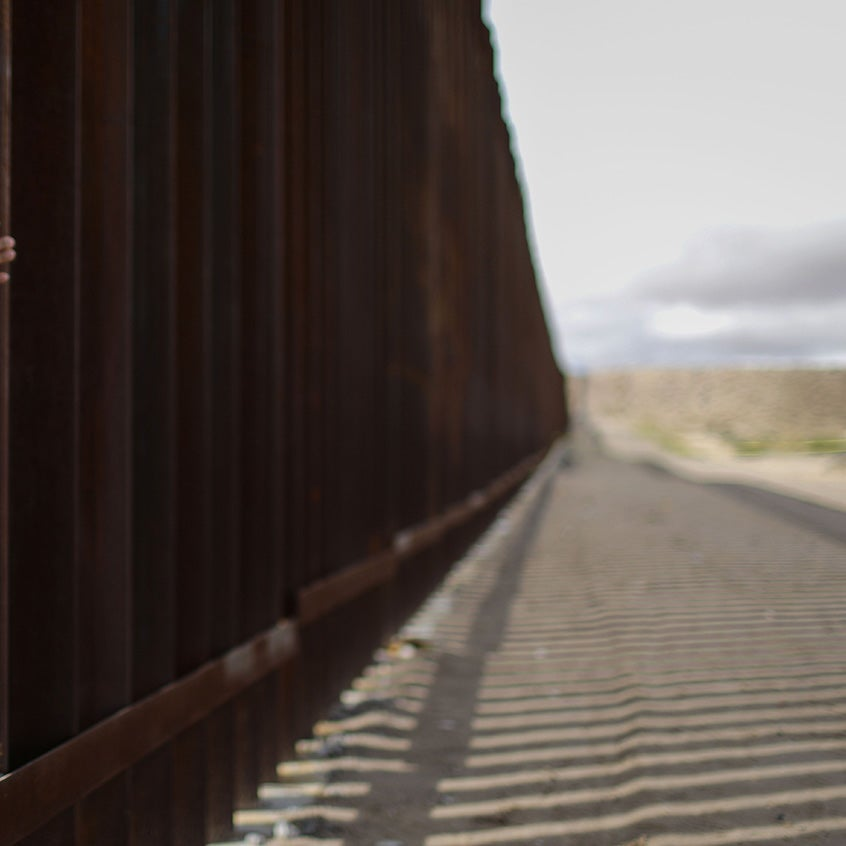 Hands reach through the wall at the US Mexico border